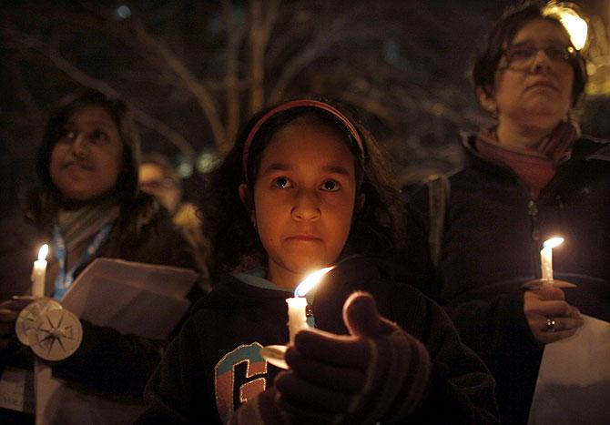 Una niña sostiene una vela en un homenaje a las víctimas en Nueva York. | Reuters