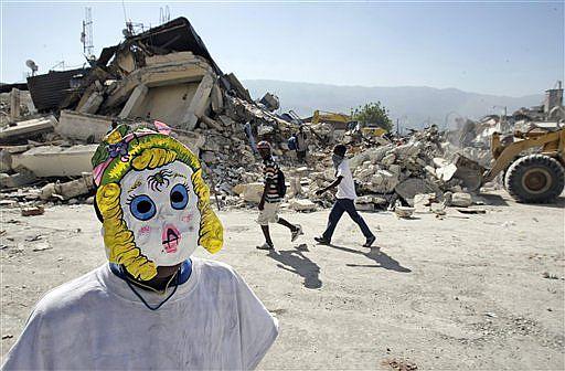 Un niño se oculta con una máscara de carnaval en las ruinas de Puerto Príncipe. | AP