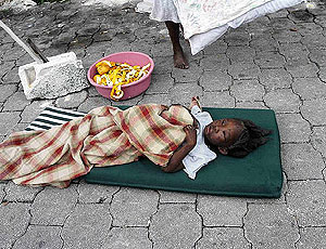 Una niña, víctima del seísmo, tendida en un cojín en las calles de la capital de Haití. | AFP