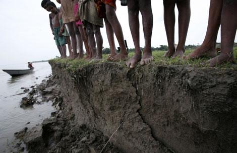 Un grupo de niños de Manikgonj (Bangladesh) que han perdido sus hogares debido a la erosión, junto a la orilla del río Jamuna.   AP