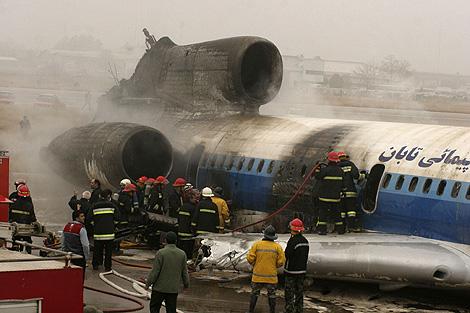 Los bomberos trabajan en la extinción del incendio en el avión estrellado en Mashad. | Reuters