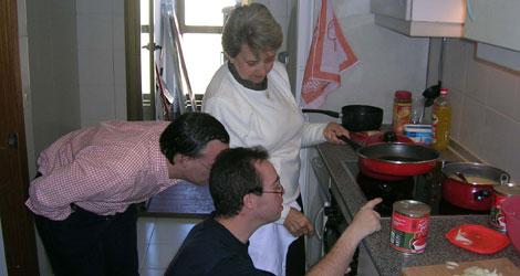 Dos jóvenes junto a una profesional en la cocina de uno de los pisos. | Servimedia
