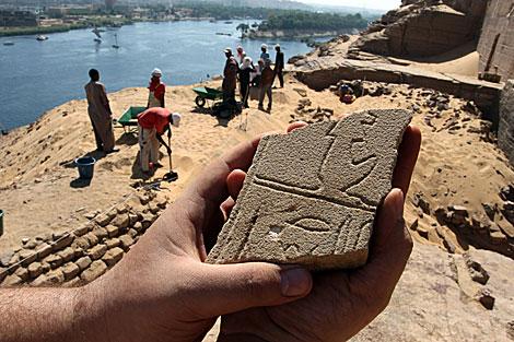 Un arqueólogo muestra una pieza con inscripciones hallada en la excavación. | Manuel Cuevas