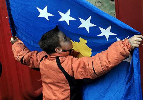 Un niño albano kosovar besa la bandera Kosovo en el aniversario de la independencia. | Efe