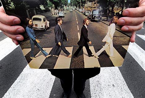 Un guía turístico sujeta una foto del disco 'Beatles Abbey Road' en la misma célebre calle londinense.   Andy Rain