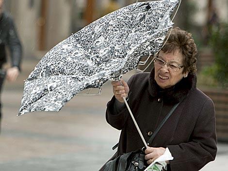 Una mujer, sorprendida por el viento. | Efe