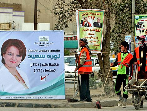 Trabajadores iraquíes observan el cartel de la candidata Nora Said en el centro de Bagdad.   Efe