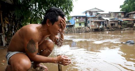 Un hombre se lava la cara con agua contaminada de un río en Yacarta. | Efe