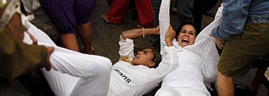 Dos Damas de Blanco son conducidas al vehículo policial.   AP