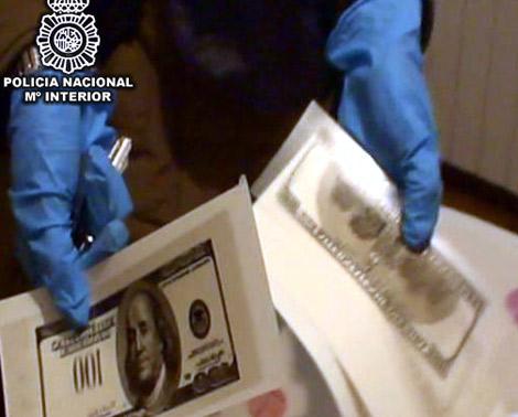Un agente de policía muestra los billetes falsos de 100 dólares.