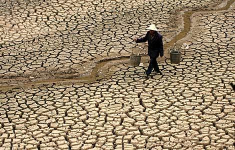 Un agricultor cruza el lecho de un río seco en Luliang, en la provincia de Yunnan. | Efe