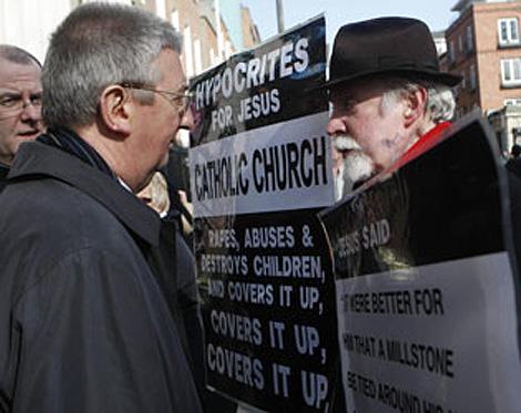 Manifestantes muestran sus carteles al arzobispo irlandés.   The Irish Times