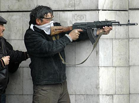 Un hombre sin identificar apunta su arma en las calles de Bishkek, Kirguistán. | Ap