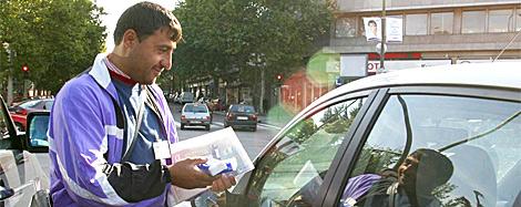 Un hombre vende el periódico 'La farola' en un semáforo de Madrid. | Diego Sinova
