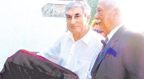 Darío Rivas (dcha.) junto a un vecino que lleva los restos de su padre. | Gentileza de Clarín