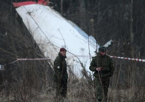 Dos oficiales rusos vigilan los restos del avión en Smolensk (Rusia). | Reuters