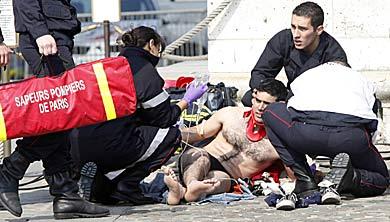 Personal sanitario atiende a la persona herida tras caer del monumento. | AFP