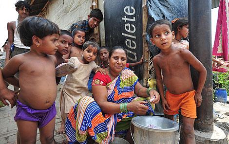 Una mujer rodeada de sus hijos prepara la comida   J.C.C.