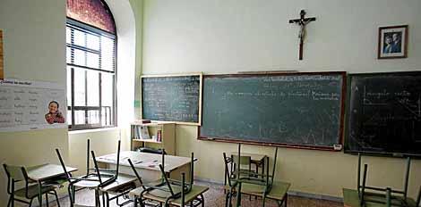 Un aula de un colegio español con un crucifijo sobre su pizarra. | EL MUNDO