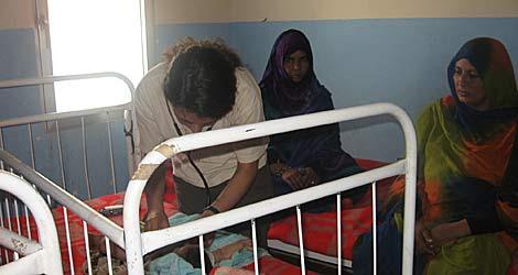 Una cooperante española atiende al bebé enfermo. | R.Q