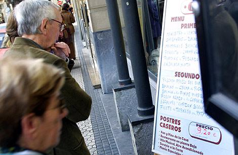 Unos viandantes observan el menú del día de un restaurante.   ELMUNDO.es