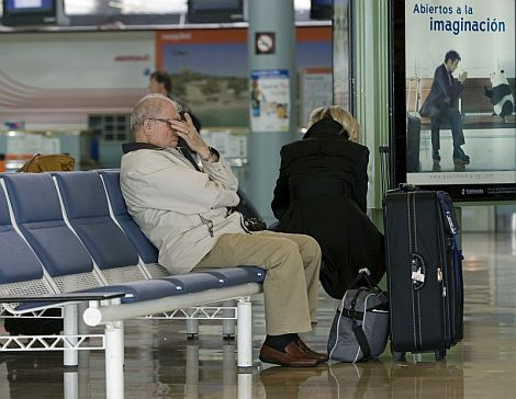 Dos pasajeros esperan información en el aeropuerto de Asturias. | Efe