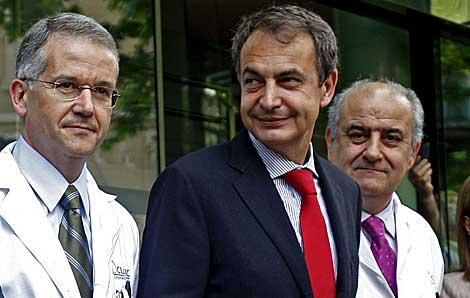 Zapatero, a las puertas del Clínic, entre dos doctores. | Efe