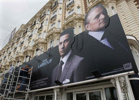 Trabajadores del festival con el cartel de la película 'Wall Street, money never sleeps' de Oliver Stone.   Yves Herman