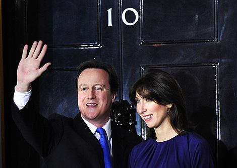 El nuevo premier, David Cameron, junto a su mujer, entra en Downing Street. | Reuters