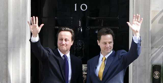 David Cameron y Nick Clegg saludan desde la puerta del número 10 de Downing Street. | Efe