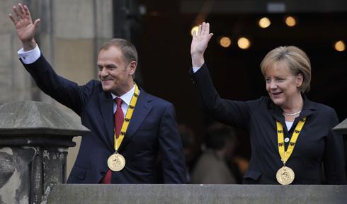 Tusk y Merkel, tras la entrega del premio. | Afp