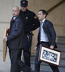 Dos escoltas sacan dos cuadros del despacho de Garzón. | Reuters