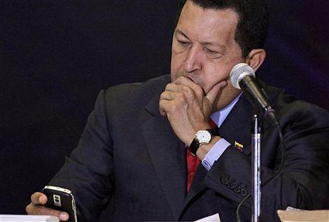 Chávez observa su teléfono móvil durante un acto público en Caracas. | AP