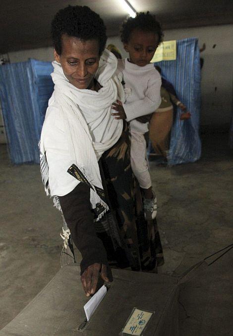 Una mujer sujeta a su hijo mientras vota en un colegio electoral de Addis Abeba. | Efe