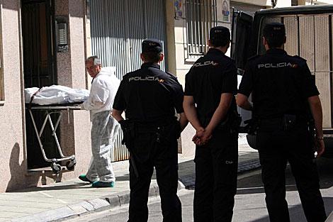 La policía contempla cómo sacan de la vivienda el cuerpo de la mujer asesinada. | Miguel Cabrera