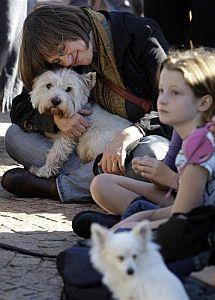 Una mujer abraza a su perro durante el concierto.   AP