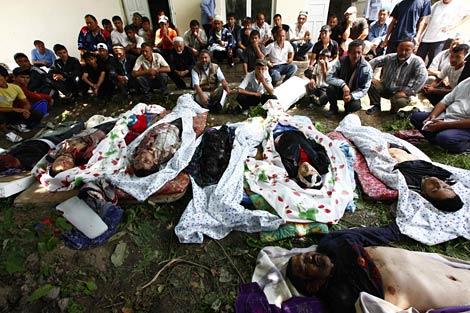 Miembros de la minoría uzbeka sentados ante algunos cadáveres en un suburbio de Osh.   Afp
