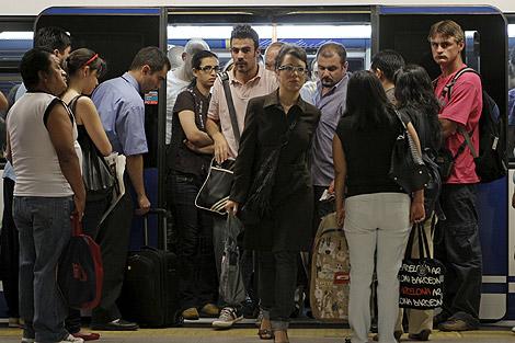 Varios pasajeros salen del vagón del metro.   Efe