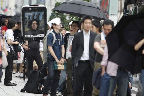 Varios clientes hacen cola frente a una Apple Store de Japón.   Ap