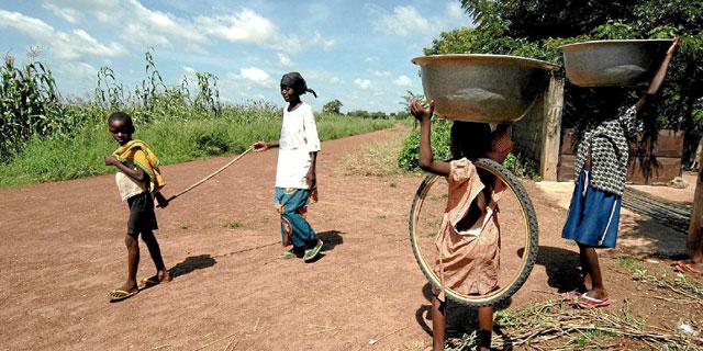 Un menor hace de guía de una persona ciega en Togo. | C. Sánchez