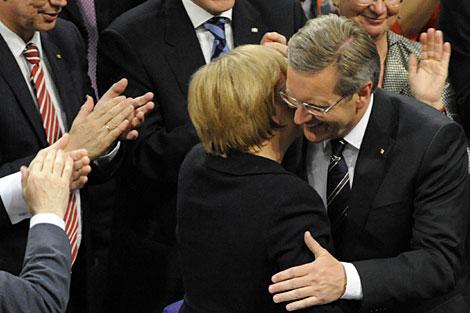 El nuevo presidente alemán es felicitado por la canciller Angela Merkel.   AFP