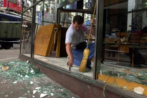 Un empleado recogiendo los desperfectos de un negocio | AP