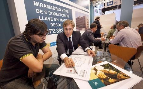 Un joven se interesa por la compra de una vivienda en un salón inmobiliario. | Gonzalo Arroyo