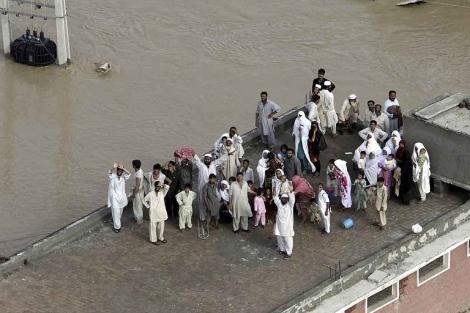 Varios vecinos de Nowshera esperan a ser rescatados en los tejados de sus casas. | AP