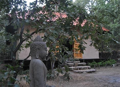 Una imagen de buda y al fondo el Dojo (templo)/ R.B.