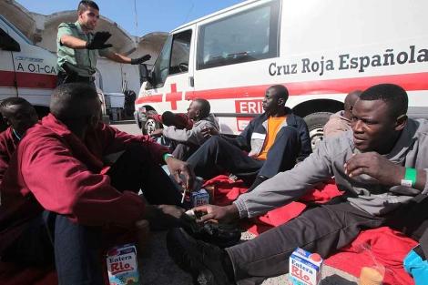 Un agente junto a algunos de los inmigrantes trasladados al puerto de Algeciras. | F. Ledesma