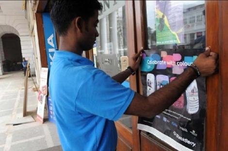 Un joven coloca un cartel de BlackBerry en una tienda india. | Afp