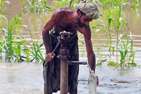 Un damnificado recolecta agua potable desde una grifo en una calle inundada en Pakistán | EFE
