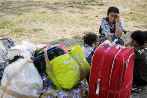 Gitanos rumanos expulsados de Francia descansan en el aeropuerto de Bucarest. | Efe