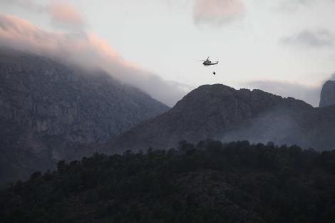 Un helicóptero trabaja en la extinción del incendio. | Brutopictures